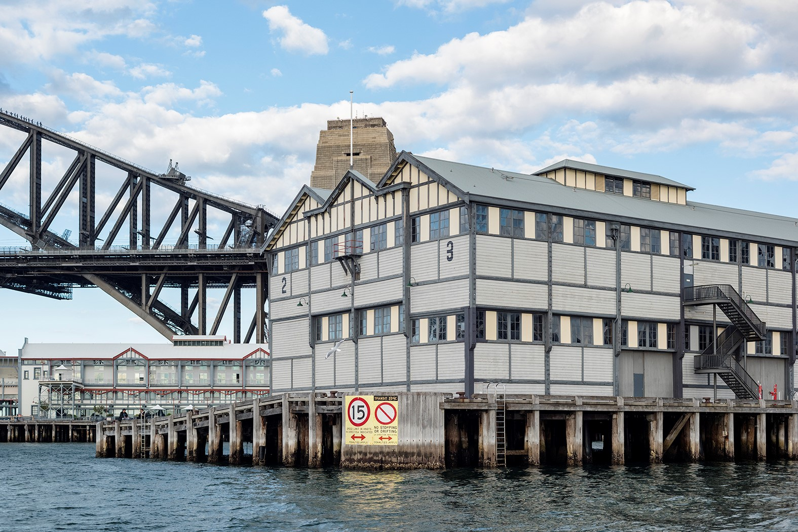 Building on sydney waterfront with harbour bridge in background